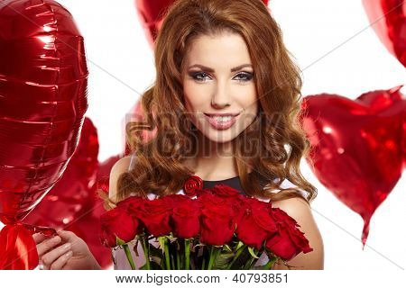 young beautiful woman smelling a bunch of red roses