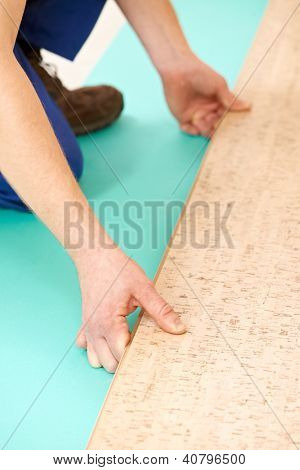 Close-up process of cork boards laying during indoors flooring work