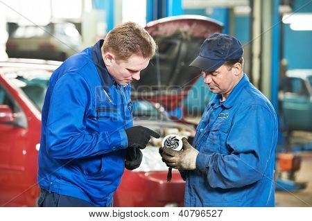 two mechanic engineers examining spare part of internal combustion engine of automobile car at repair service station