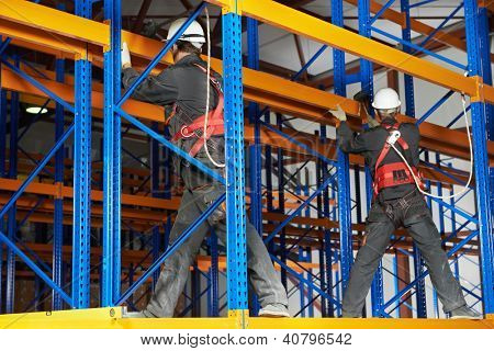 team of two warehouse workers in uniform with power tool drilling hole during rack arrangement erection work