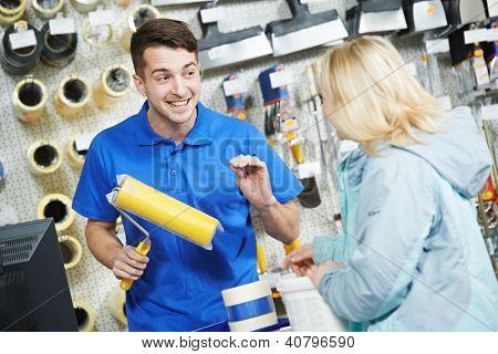 Asistente vendedor ayuda comprador demostrando el rodillo de pintura para pintar en ferretería