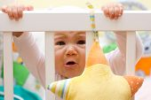 image of scared baby  - Portrait of crying baby girl in her cot.