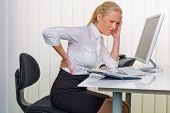 stock photo of spinal column  - a woman with back pain from sitting so long in the office - JPG