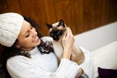 foto of attic  - Young woman in winter in a cozy attic with her cat - JPG