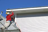 stock photo of soffit  - a worker atop a tall ladder uses a nail gun to attach the fascia board on a house - JPG