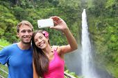 Couple tourists taking self portrait with camera phone on Hawaii, Big Islands, Akaka Falls. Happy ch