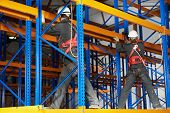 team of two warehouse workers in uniform with power tool drilling hole during rack arrangement erect