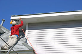 pic of soffit  - a worker atop a tall ladder uses a nail gun to attach the fascia board on a house - JPG