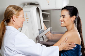 foto of mammography  - Mature female doctor assisting young patient during mammogram x - JPG