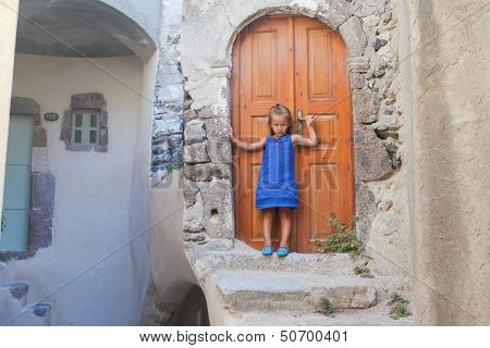 Little Cute Girl In Medieval Village Of Emporio At Santorini Island, Greece