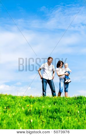 Happy Young Family On Green Grass Over Sky