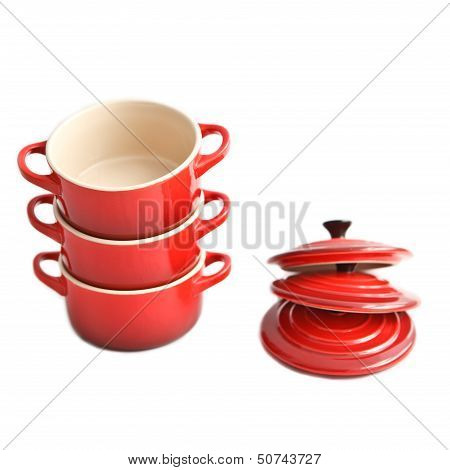 Three red cocottes (small casserole) with covers on a white background
