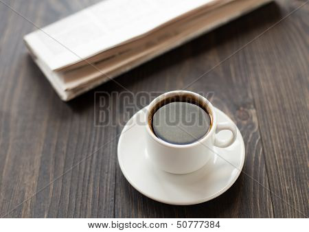Newspaper and cup of coffee on table