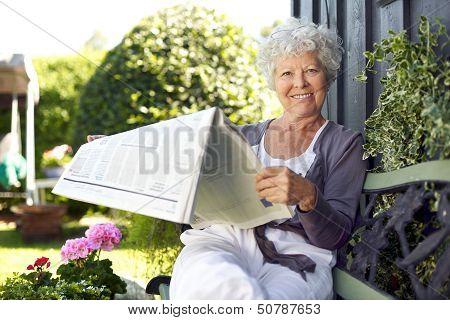 Senior Woman Reading Newspaper In Backyard Garden