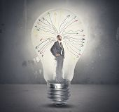 stock photo of enlightenment  - Concept of genius businessman tkinking in a light bulb - JPG