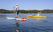 stock photo of kayak  - A man and wife getting exercise together paddleboarding and kayaking on a beautiful lake.