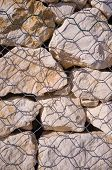 stock photo of rip-rap  - Detail take of stones behind the mesh of a gabion wall - JPG