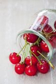 picture of picking tray  - Freshly picked ripe cherries with stem and leaves in front of a preserving jar filled with cherries - JPG