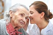 stock photo of hospice  - Female nurse is speaking in senior woman ear - JPG