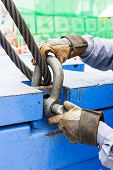 picture of shackles  - Close up worker fitting bolt anchor shackle with wire rope sling on crane counter weight - JPG