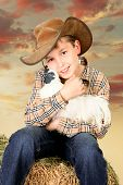 pic of bantams  - A country farm boy sitting on a lucerne bale and holding a bantam chicken at sunset - JPG