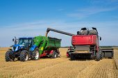 stock photo of farm land  - Harvest machine loading seeds in to trailer - JPG