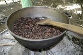 stock photo of pot roast  - large pot containing ripe coffee beans that are roasting over an outdoor fire - JPG