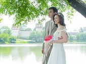 pic of wedding couple  - wedding couple near the water and monastery - JPG