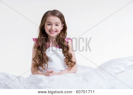 Happy Little Girl Awake And Sitting In The Bed.