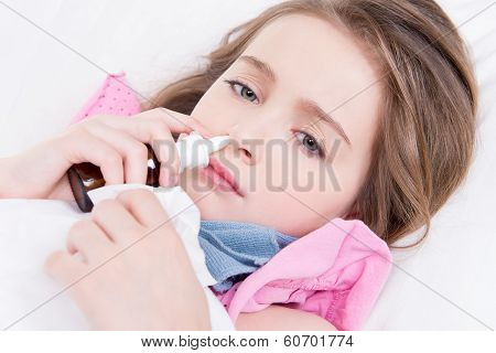Little Girl With Bad Cold Using Nasal Drops.