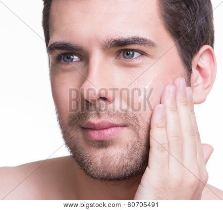 Young Handsome Man Applying Cream.