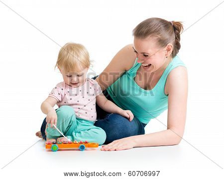 Mother And Baby Girl Having Fun With Musical Toy. Isolated On White Background