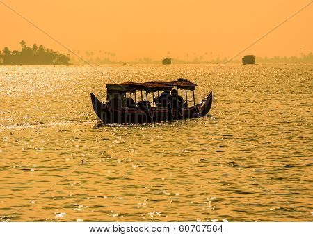 Sunset Silhouette Scene Of A Boat From The Backwaters Of Kerala, India.