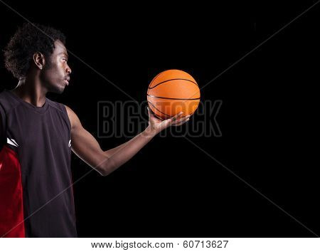 Portrait of a basketball player holding a ball against dark background