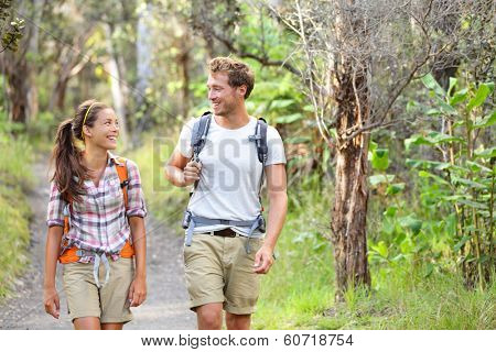 Hikers - hiking people walking happy in forest. Hiker couple laughing and smiling. Interracial couple, Caucasian man and Asian woman on Big Island, Hawaii, USA.
