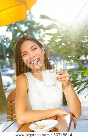 Woman drinking coffee at cafe. Young woman sitting at sidewalk cafe table enjoying hot drink of coffee or tea. Beautiful happy smiling mixed race Asian Caucasian female model in Berlin, Germany.