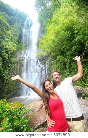 Hawaii tourist people couple happy by waterfall during travel on the famous road to Hana on Maui, Hawaii. Ecotourism concept image with happy backpackers. Interracial Asian / Caucasian young couple.