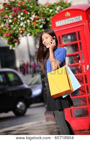 London woman talking happy on smartphone shopping holding shopping bags by red phone booth. Female shopper using mobile smart phone smiling in London, England, United Kingdom. Mixed Asian Caucasian.