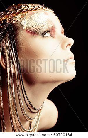 Art project: beautiful woman with golden make-up. Jewelry, make-up. Fashion.