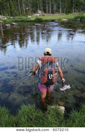 Woman Backpacker Wading Across River