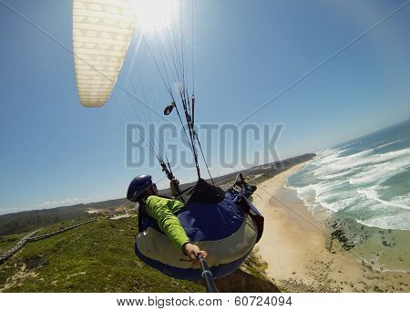 Paraglider pilot in flight with a white wing