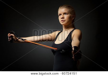 Woman exercising with resistance band on dark