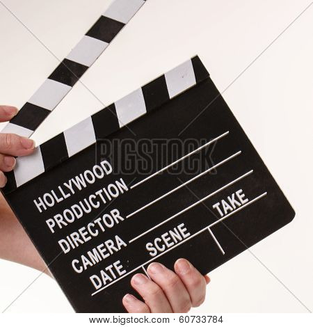 Movie Flapper In Woman´s Hands On White Background