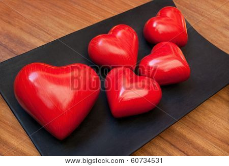 Red Wooden Valentine Hearts On Black Plate Over Brown Woody Table