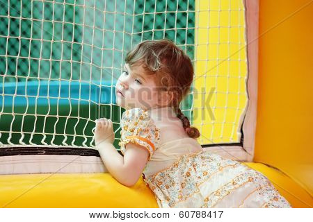 Little Beautiful Girl In Dress Stands In Yellow Bouncy Castle And Looks Through Net
