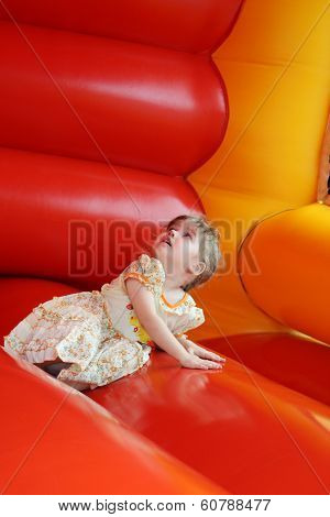 Little Beautiful Happy Girl Lies In Red Bouncy Castle And Looks Up