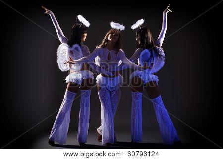 Trio of sexy female dancers posing under UV light