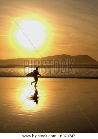 Silhouetted Surfer At Sunset