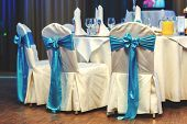 stock photo of wedding feast  - White wedding chairs decorated blue bows at restaurant - JPG