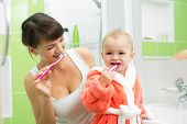 stock photo of toothbrush  - mother with baby brushing teeth in bathroom - JPG